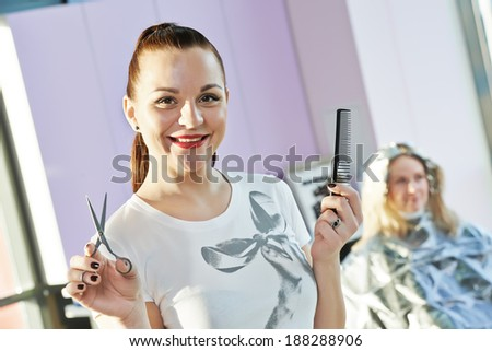 Happy female hairdresser with comb and scissors at beauty parlour with client - stock photo