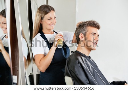Happy female hairstylist setting client's hair at parlor - stock photo