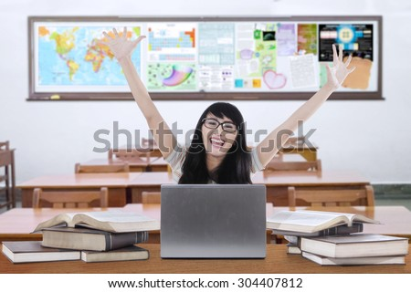Happy female high school student studying in the classroom with laptop and raise hands - stock photo