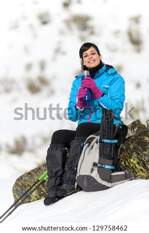 Happy female hiker sitting and resting with hot drink on hands on winter snowy mountains. Caucasian woman hiking beautiful traveler on winter vacations. - stock photo