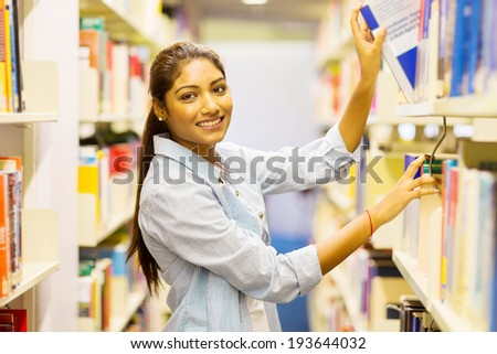 happy female indian college student pulling a book off shelf in library - stock photo