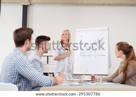 Happy Female Leader Presenting a Business Progress Chart to the Team at the Boardroom Inside the Office. - stock photo