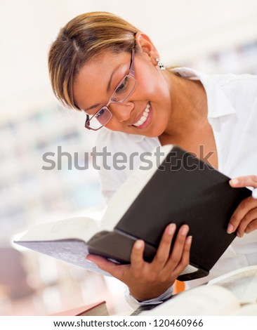 Happy female librarian holding a book and reading it - stock photo