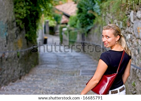 happy female looking back while walking down romantic stairs - stock photo