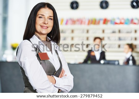 Happy female manager worker standing at hotel - stock photo