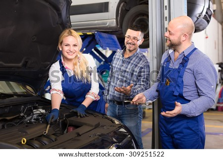 Happy female mechanic repairing a car with a wrench while her male colleague and owner are consulting her - stock photo