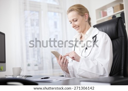 Happy Female Medical Doctor Sitting at her Table and Browsing Something on her Mobile Phone - stock photo