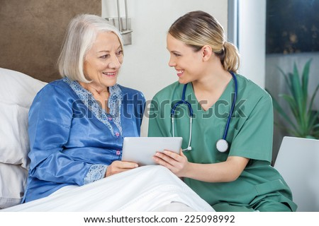 Happy female nurse and senior woman discussing while using tablet PC in bedroom at nursing home - stock photo