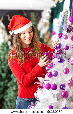 Happy female owner decorating Christmas tree at store - stock photo