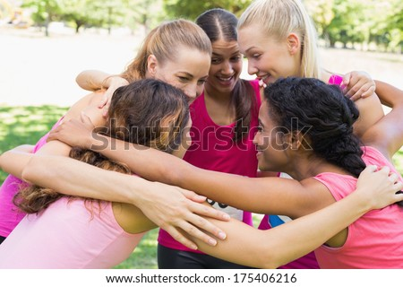 Happy female participants of breast cancer marathon forming huddle in park - stock photo