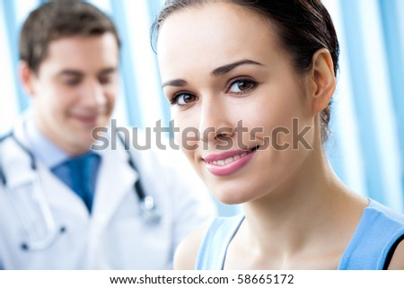 Happy female patient and doctor at office - stock photo