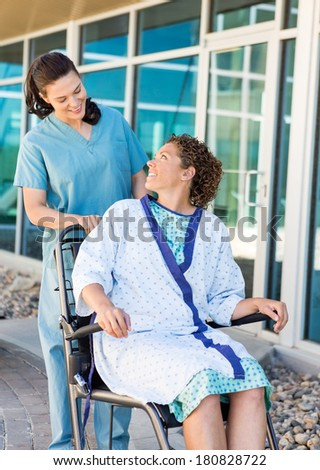 Happy female patient looking at friendly nurse while sitting on wheelchair at hospital courtyard - stock photo