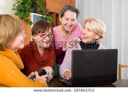 Happy female pensioner studying laptop and internet  at home