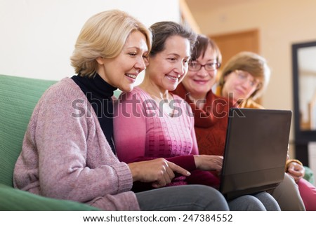 Happy female pensioner studying laptop together  at home - stock photo