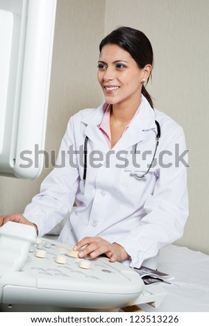 Happy female radiologist operating ultrasound machine at clinic - stock photo