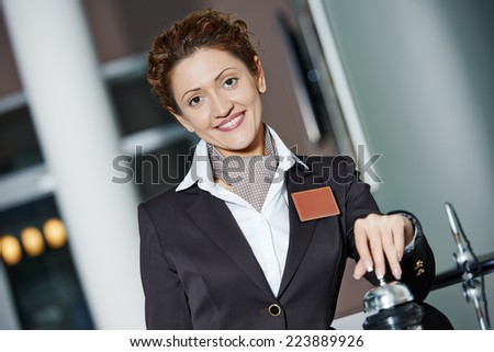 Happy female receptionist worker standing at hotel counter with bell - stock photo