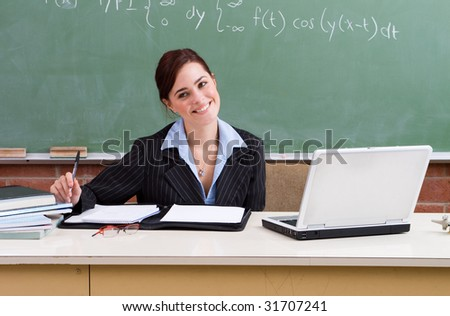 happy female school teacher in classroom