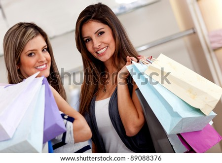 Happy female shoppers at a shopping center with bags