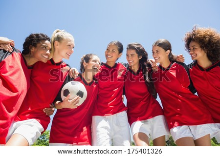 Happy female soccer team with ball against clear blue sky - stock photo