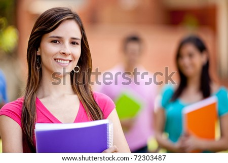 Happy female student carrying notebooks outdoors - stock photo