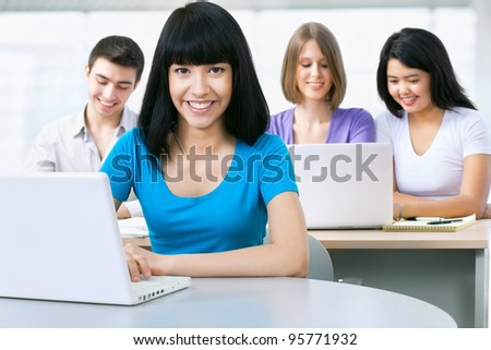 Happy female student looking at camera - stock photo