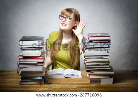 Happy female student with glasses and lots of books at a table is listening - stock photo