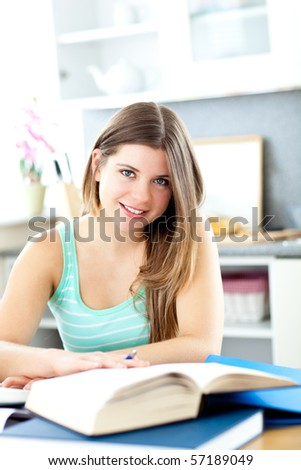 Happy female teenager studying in the kitchen at home