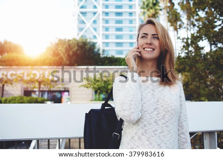 Happy female traveler talking on mobile phone about wonderful trip while standing outdoors in spring day, young woman with beautiful smile having cell telephone conversation during her free time  - stock photo