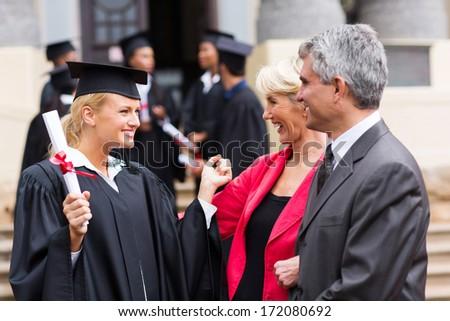 happy female university graduate with parents at graduation ceremony - stock photo