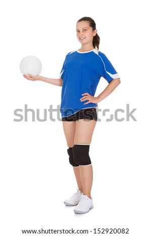 Happy female volleyball player holding ball on white background - stock photo
