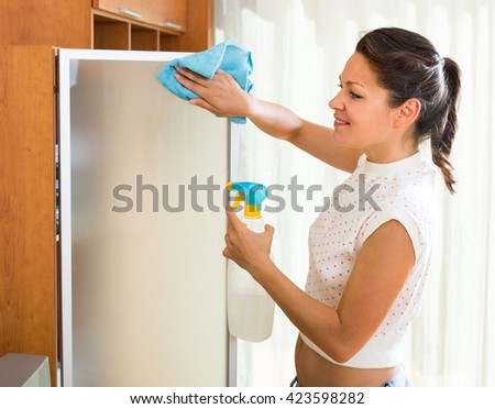 Happy female washing glass with sprayer and rag