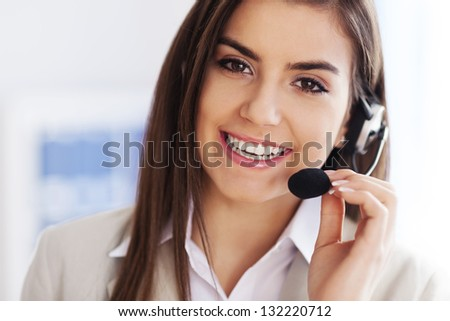 Happy female wearing headset and looking at camera - stock photo