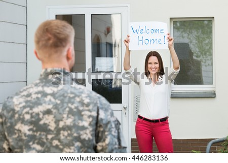 Happy Female Welcoming Her Husband Home From Army Leave - stock photo