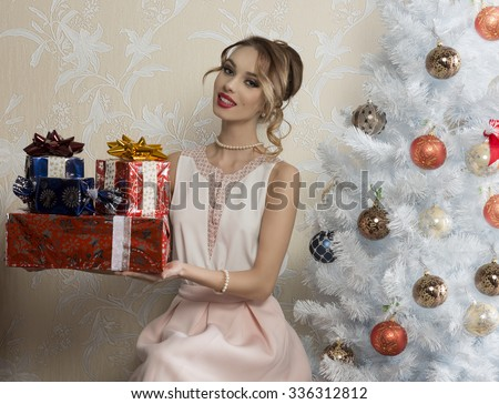 happy female with elegant dress and hair-style sitting near decorated tree in Christmas night, smiling and taking some presents in the hand  - stock photo