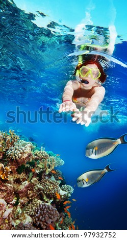 Happy female woman snorkeler diving among corals and fishes