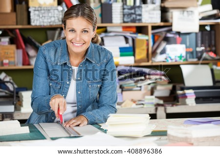 Happy Female Worker Cutting Paper At Table - stock photo