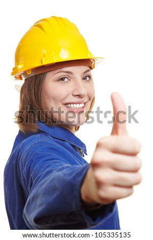 Happy female worker in blue overall and hardhat holding thumbs up