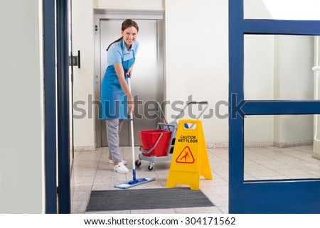 Happy Female Worker In Uniform Cleaning Floor With Mop - stock photo