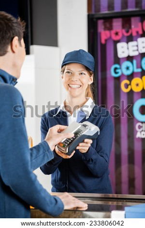 Happy female worker taking payment from man through NFC technology at cinema concession stand - stock photo