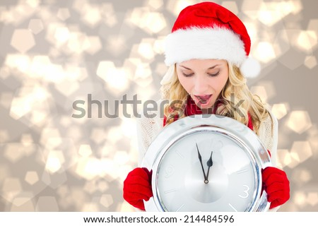 Happy festive blonde with clock against light glowing dots design pattern - stock photo
