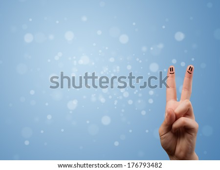 Happy finger smileys faces on hand with empty blue bokeh background - stock photo
