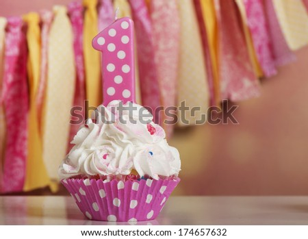 Happy first birthday cupcake in pink and yellow - stock photo