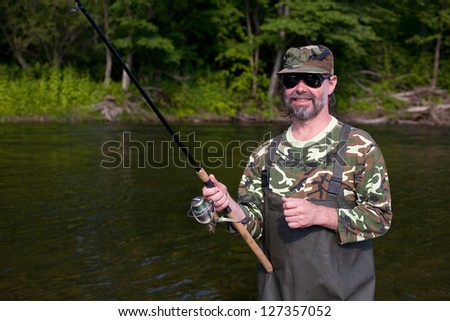 Happy fisherman catches of salmon in the river. - stock photo