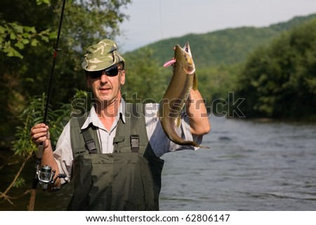 Happy fisherman caught a salmon (pink salmon) on the River - stock photo