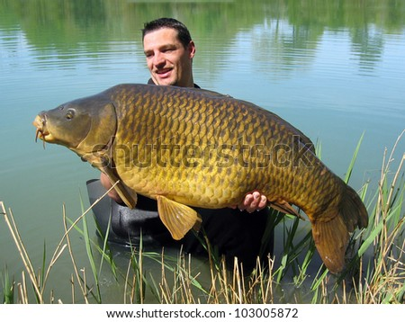 Happy  fisherman holding a beautiful common carp - stock photo