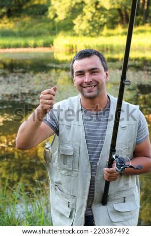 Happy fisherman holding a fish  - stock photo