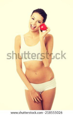 Happy Fit female in white sport underwear with red heart shaped toy - stock photo