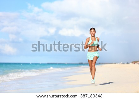 Happy fit female runner running on sand during summer travel vacation on tropical beach. Asian woman jogging doing cardio training exercising for weight loss. Happiness and wellbeing concepts. - stock photo