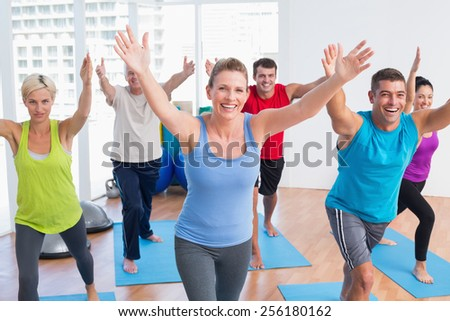 Happy fit men and women exercising in gym class - stock photo