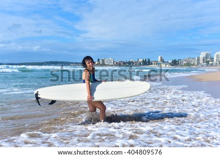 Happy fit sporty senior surfer woman wearing a swimsuit, holding her mini malibu surfboard and going out of water after surf session, smiling with toothy smile.  - stock photo